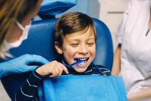 little boy brushing teeth at dentist